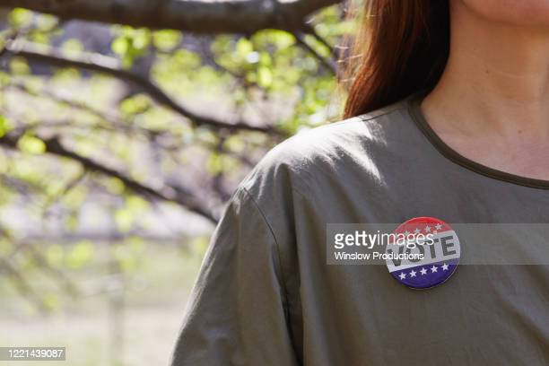 woman with vote button on her top - voting stock pictures, royalty-free photos & images