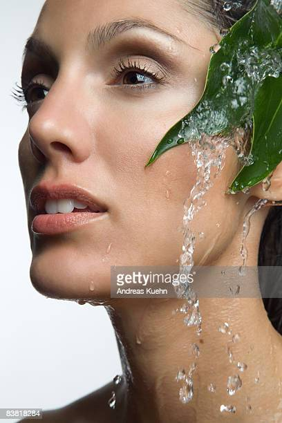 Woman with water running down face, profile.