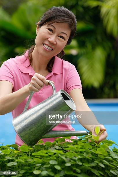 Woman with watering can, watering plants