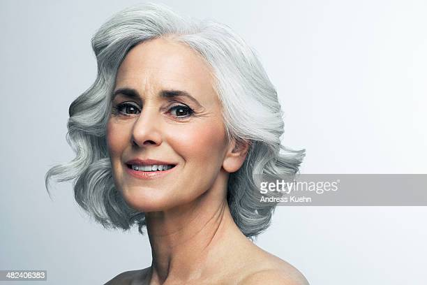 woman with wavy, grey hair smiling, portrait. - beautiful bare breasted women stock pictures, royalty-free photos & images