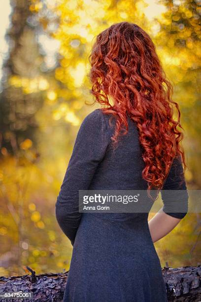 Woman with wavy red hair in autumn outdoors