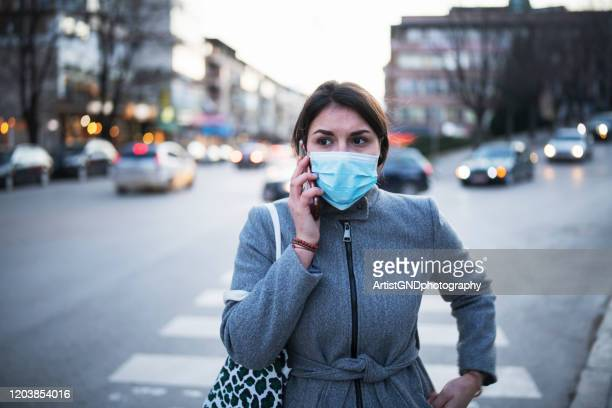 woman with wear talking on the phone. - coronavirus foto e immagini stock