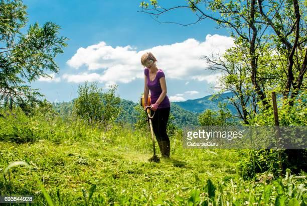 Femme avec Weed tondeuse couper l'herbe sur la prairie de montagne