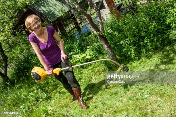 Woman With Weed Trimmer Cutting Grass On The Mountain Meadow