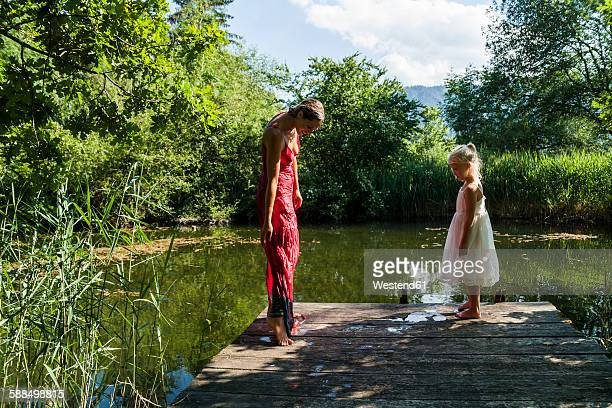 Woman with wet dress and daughter on jetty at a lake