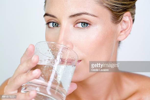 Woman with wet face drinking a glass of water