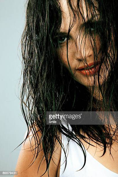 Woman with wet hair covering face