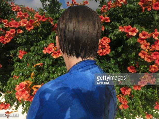 woman with wet hair standing at flowers in sunny garden - briel stock pictures, royalty-free photos & images