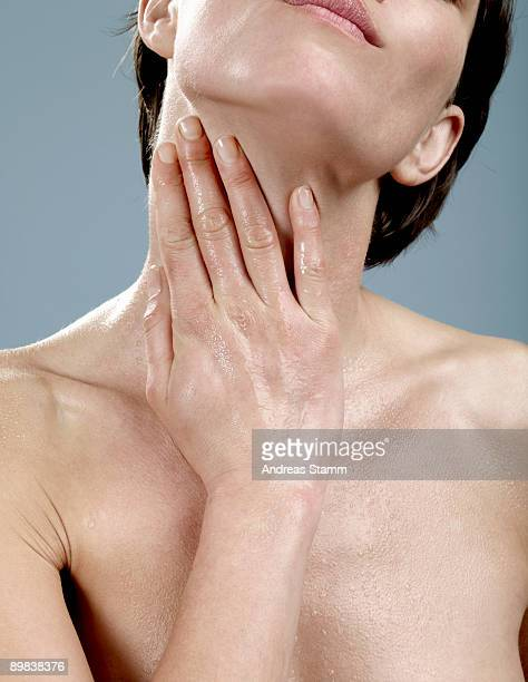 a woman with wet skin touching her neck - beautiful bare breasted women stock pictures, royalty-free photos & images