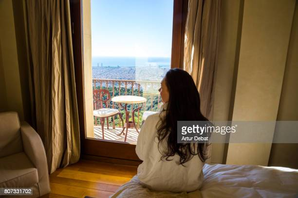Woman with white bathrobe contemplating the Barcelona cityscape view from hotel balcony during weekend days of relax and spa in a luxury place.