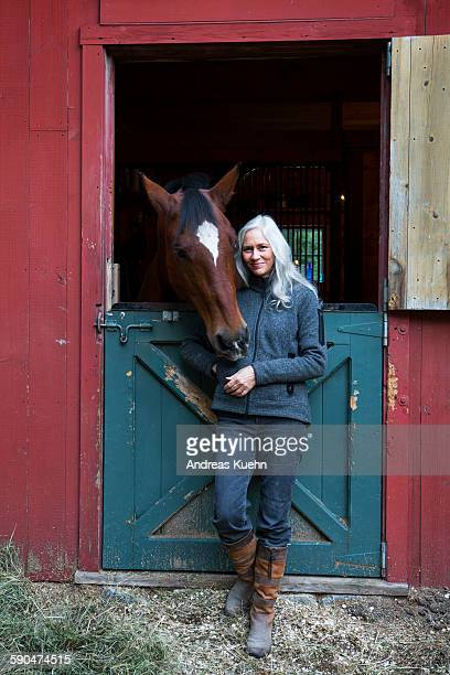Woman with white hair and her horse, full length.