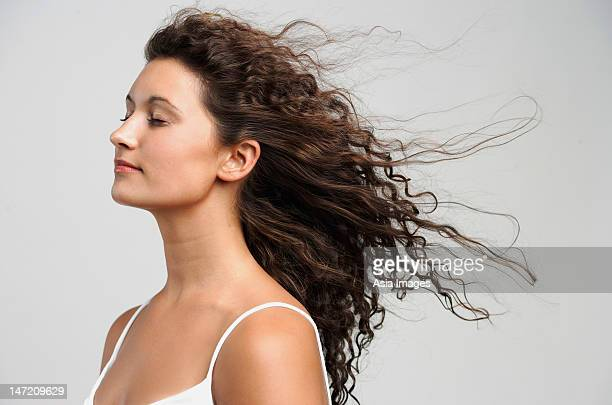 Woman with wind blowing in face, eyes closed