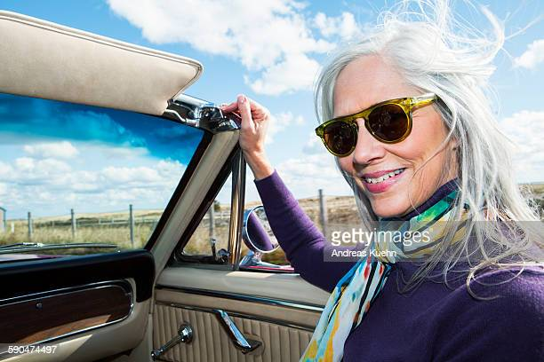 Woman with wind blown hair in a convertible.