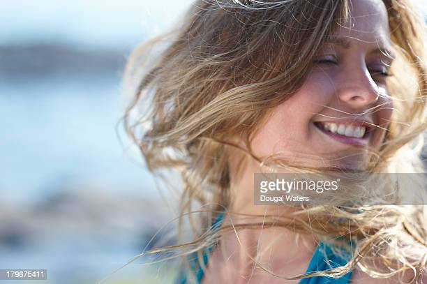 Woman with wind swept hair, smiling.