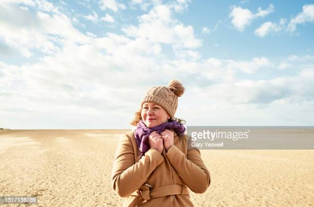 woman with windswept hair at the beach - headwear stock pictures, royalty-free photos & images
