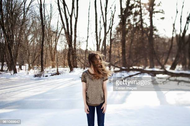 woman with windswept hair standing on snowcapped landscape - somerville massachusetts stock pictures, royalty-free photos & images
