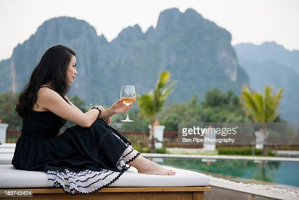woman with wine glass by poolside, vang vieng, laos - サンドレス ストックフォトと画像