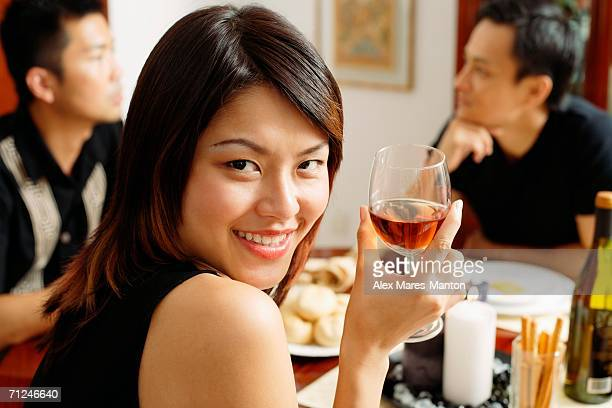 woman with wine glass, looking over shoulder, smiling - 背景に人 ストックフォトと画像
