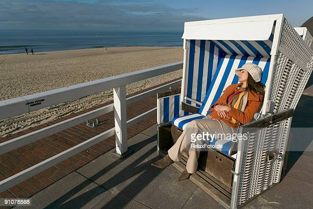 Woman with winter clothes relaxing in beach chair seaside (XXL)