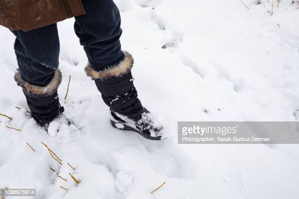 woman with winter shoes / boots on snow - snow boot stock photos and pictures