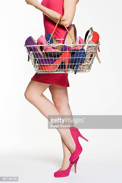 Woman with with shopping basket full of shoes