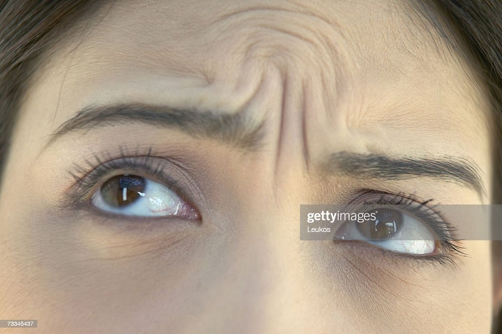 Woman with wrinkled brow, high section, close-up of eyes : Stock Photo