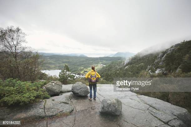 Woman with yellow backpack admiring mountain view