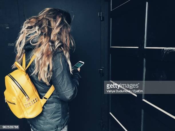Woman With Yellow Backpack Using Mobile Phone Against Door