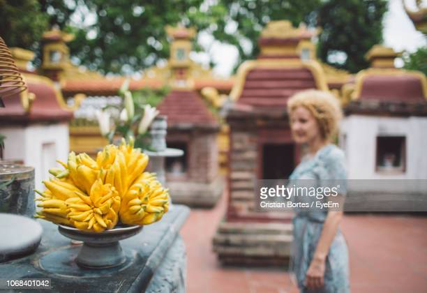Woman With Yellow Flowers At Temple