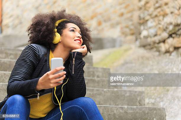 Woman with yellow headphones listening music on stairs