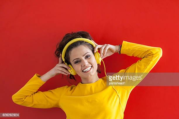 Woman with yellow headphones listening music, red background