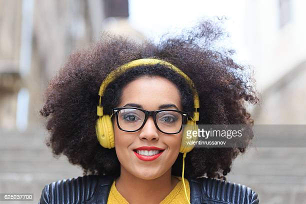 Woman with yellow headphones looking at camera