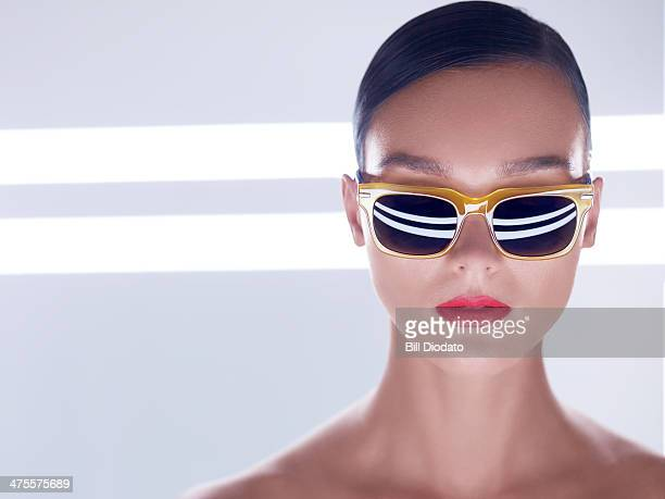 Woman with yellow sunglasses in studio