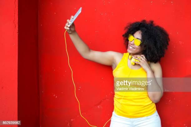 Femme avec des lunettes de soleil jaunes prenant selfie