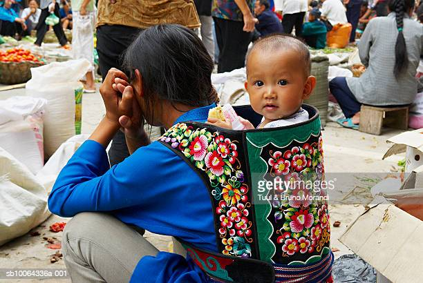 woman with young boy (9-12 months) in baby carrier on market - 12 23 months stock pictures, royalty-free photos & images