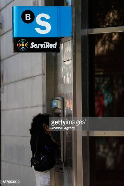 A woman withdraw cash from the ATM of a 'Banc Sabadell ' in Barcelona Spain on October 5 2017 Management of Banc Sabadell decide to move its...