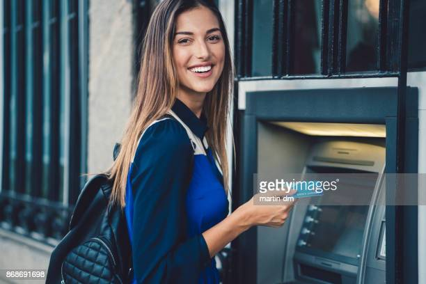 woman withdrawing money at the atm - bank stock pictures, royalty-free photos & images