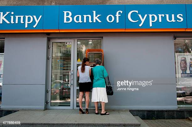 Woman withdrawing money at the Bank of Cyprus in Odessa, Ukraine. With the help of a bank employer.