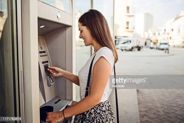 mulher que retira o dinheiro no atm ao ar livre - strip - fotografias e filmes do acervo