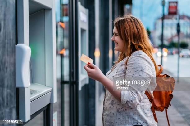 woman withdrawing money at the outdoor atm - ginger banks stock pictures, royalty-free photos & images