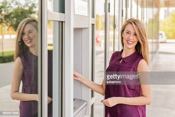 Donna di ritirare i soldi dalla carta di credito in ATM