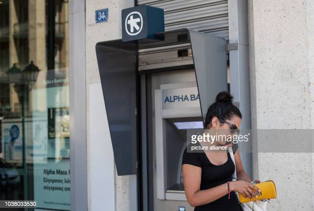 A woman withdraws cash from an ATM of Alpha Bank in Athens on the 23rd of June 2015 Photo Socrates Baltagiannis/dpa | usage worldwide