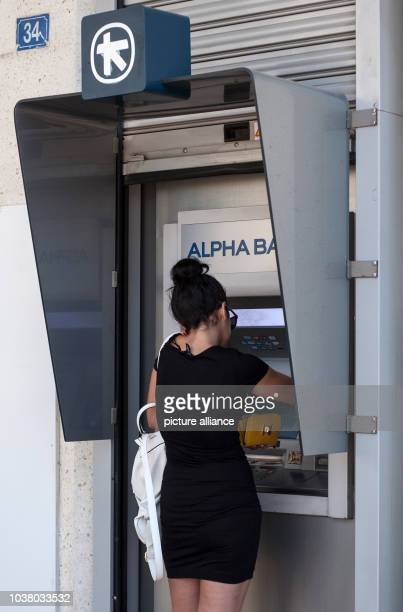 A woman withdraws cash from an automated teller machine of Alpha Bank in Athens on the 23rd of June 2015 Photo Socrates Baltagiannis/dpa | usage...