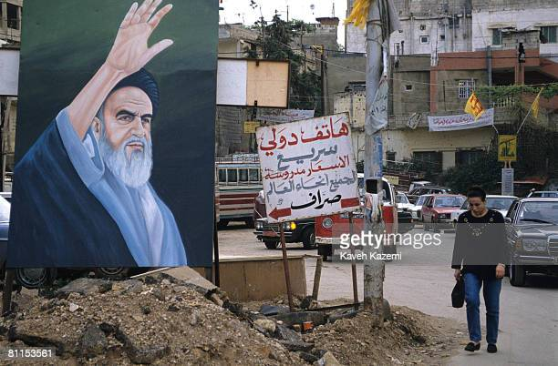 Woman without a veil passes a portrait of Ayatollah Khomeini displayed in the middle of a busy road in a Hezbollah neighborhood of southern Beirut,...