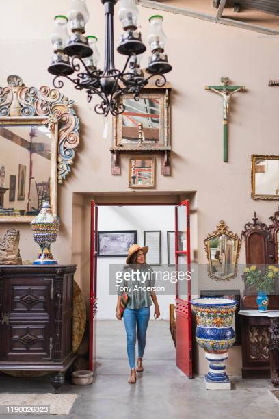 woman wlaking through entrance of antique store - antique shop stock pictures, royalty-free photos & images