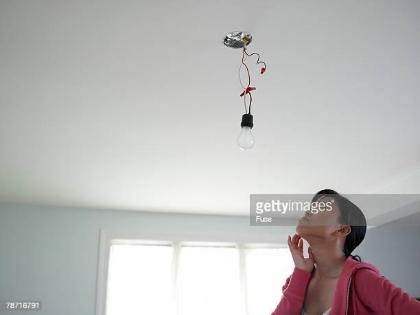 Woman Wondering How to Fix Light Fixture