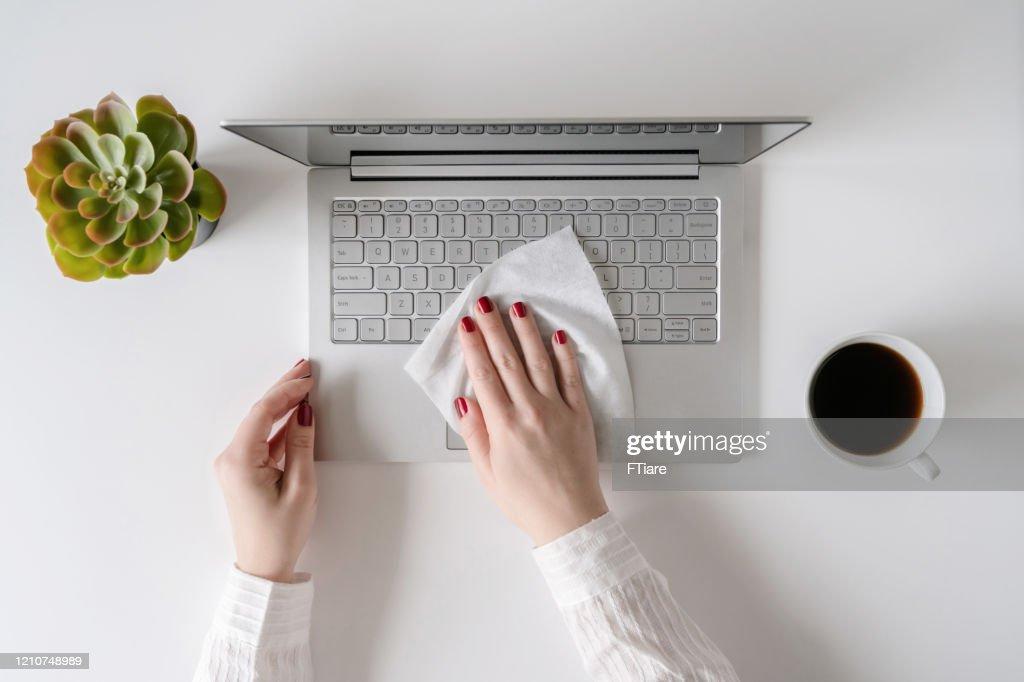 Eine Arbeiterin, die mit Antiviren-Nass putzt, wischt einen Laptop und einen Schreibtisch im Büro, bevor sie mit der Arbeit beginnt, um sich vor Bakterien und Viren zu schützen. : Stock-Foto
