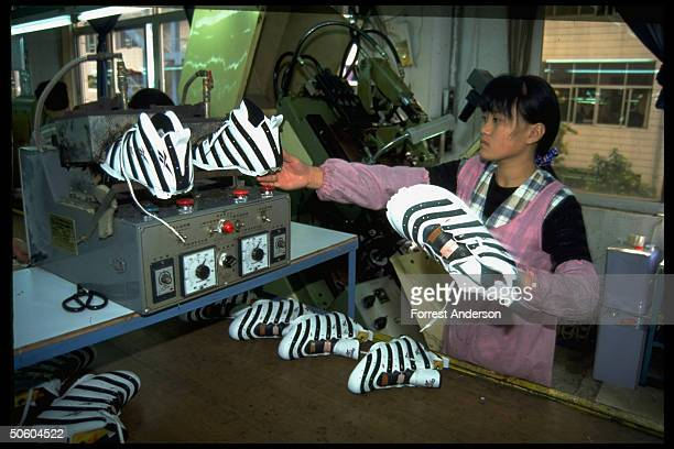 Woman worker on Reebok sneaker production line shoes made under contract w British co at Kong Tai shoe mfg plant in special economic zone city...