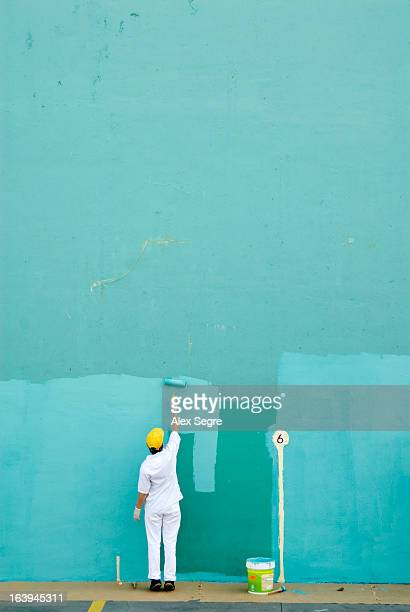 CONTENT] Woman worker painting large blank turquoise wall with roller