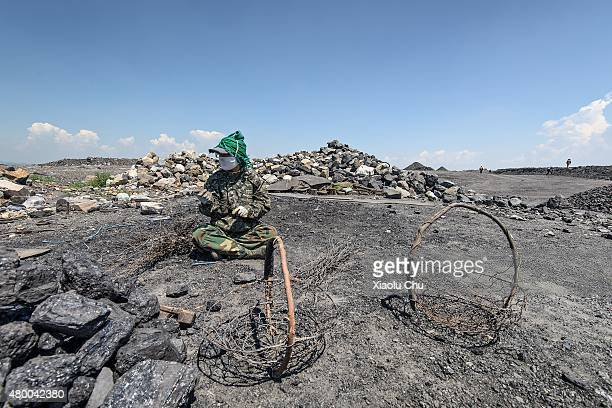 A woman worker picks up coal from slag on a hill which made by mineral waste residue from 1955 in July 04 Fuxin Liaoning Province China Fuxin is the...
